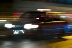 Panning shot of red taxi at night